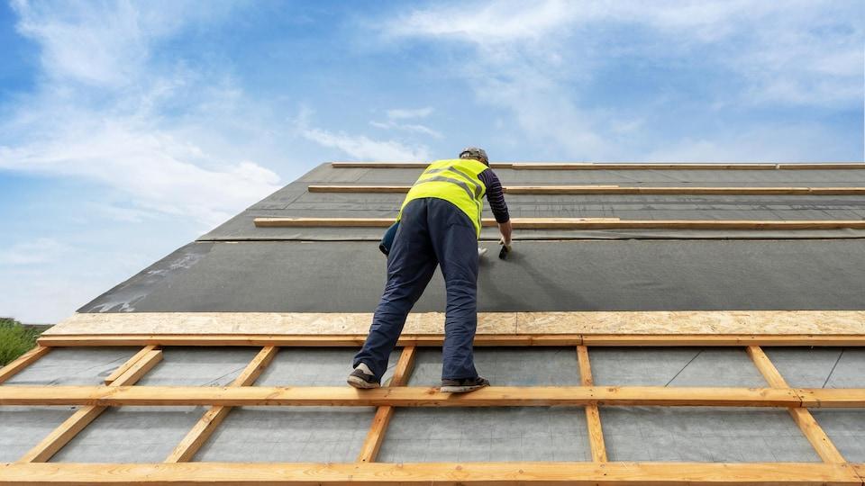 Un homme rénove le toit d'une maison.