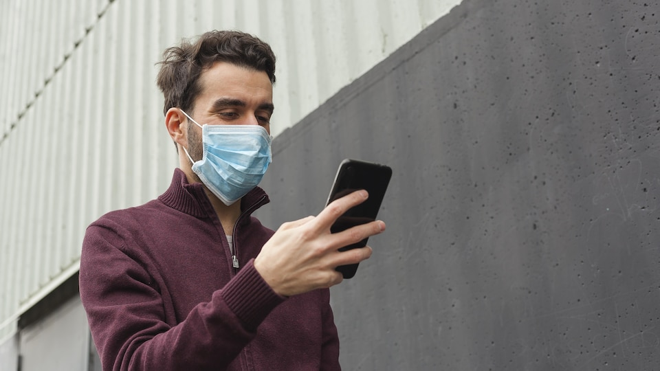 Un homme portant un masque chirurgical marche en regardant son téléphone intelligent.