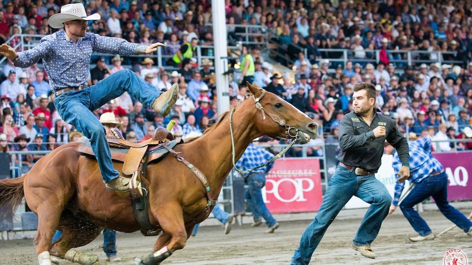 Homme sur un cheval et d'autres gens dans l'arène.