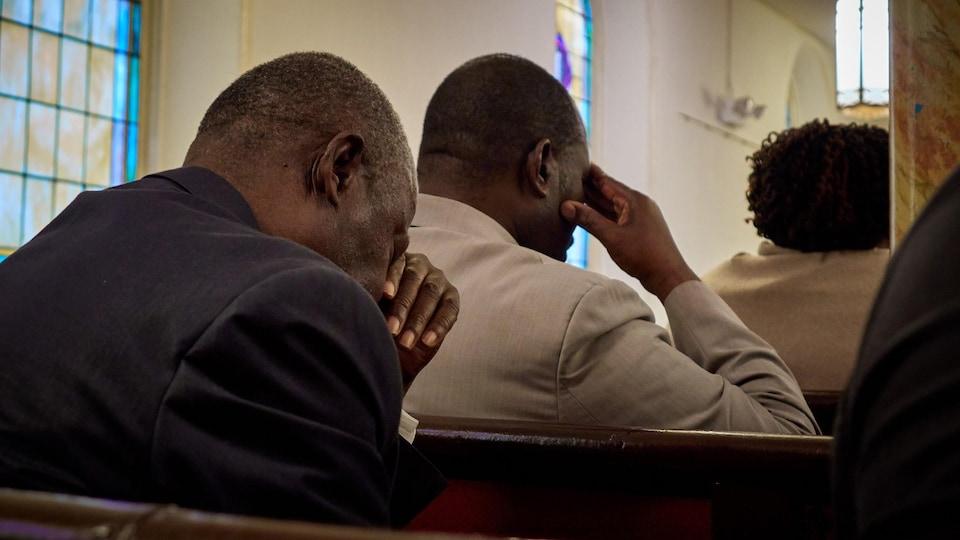 On voit de dos des hommes qui prient, assis, dans l'église haïtienne d'expression française de Brooklyn.