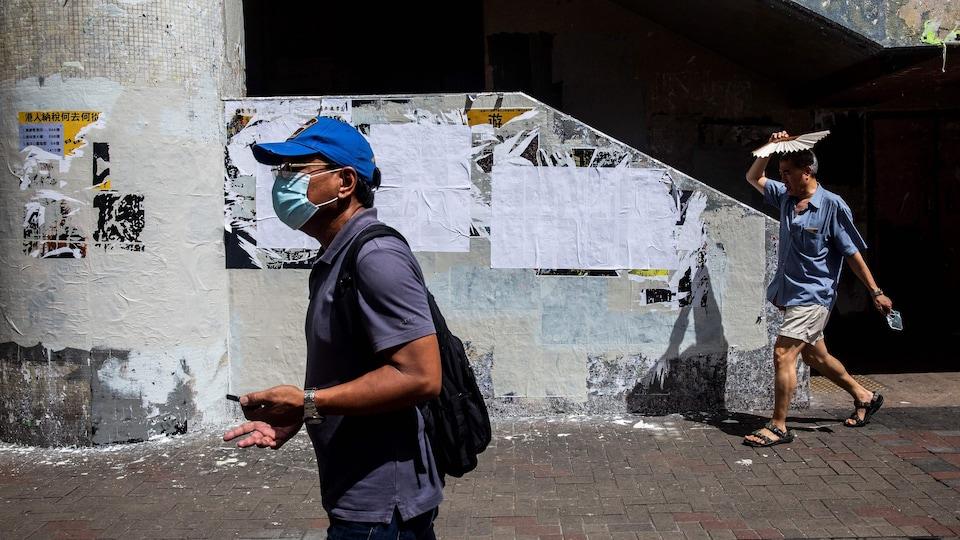 Un homme passe avec un masque, l'autre se protège du soleil avec un éventail.