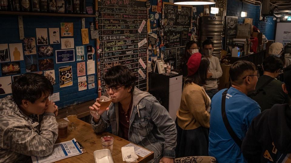 Des clients boivent dans un bar bondé de Hong Kong.