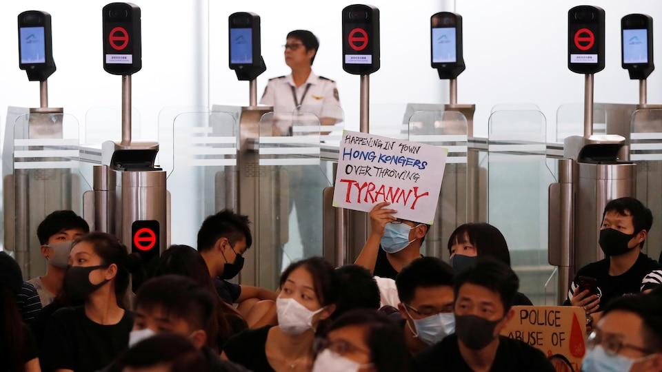 Des manifestants bloquent l'accès à un comptoir d'enregistrement à l'aéroport.