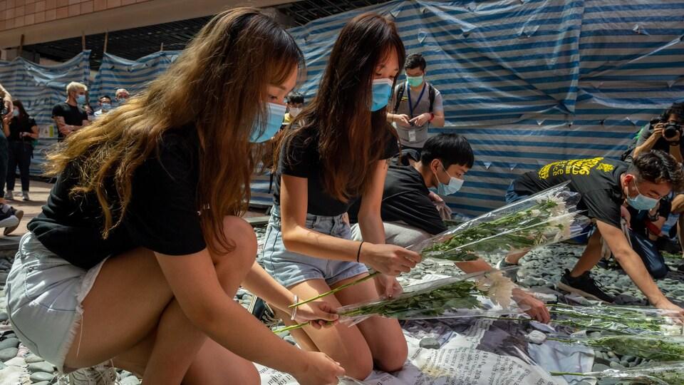 Des jeunes portant des masques déposent des fleurs.