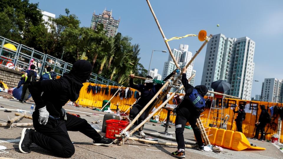 Des manifestants vêtus de noir utilisent une catapulte de fortune.