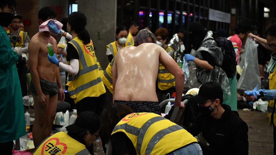 Des manifestants se déshabillent pour être traités par des bénévoles médicaux.