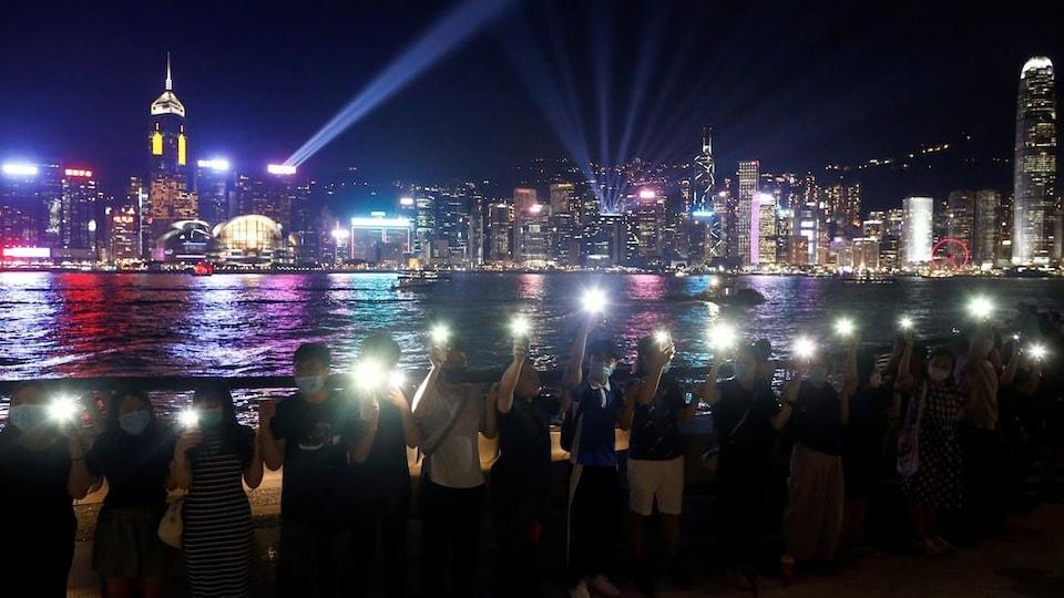 Des gens tiennent leur téléphone devant la ligne d'horizon de Hong Kong.