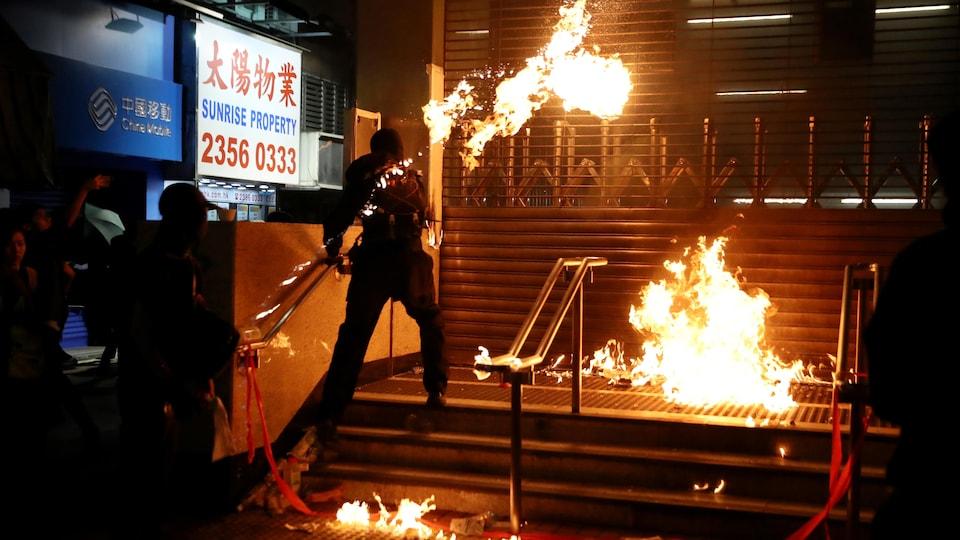 Quelques personnes vêtue de noir se tiennent près de flammes.