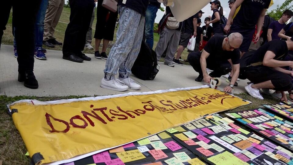 Des personnes préparent des banderoles de manifestations, dont une mentionne en anglais «ne tirez pas sur les étudiants».