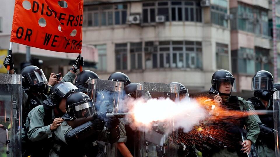 Des policiers tirent du gaz lacrymogène afin de disperser des manifestants.