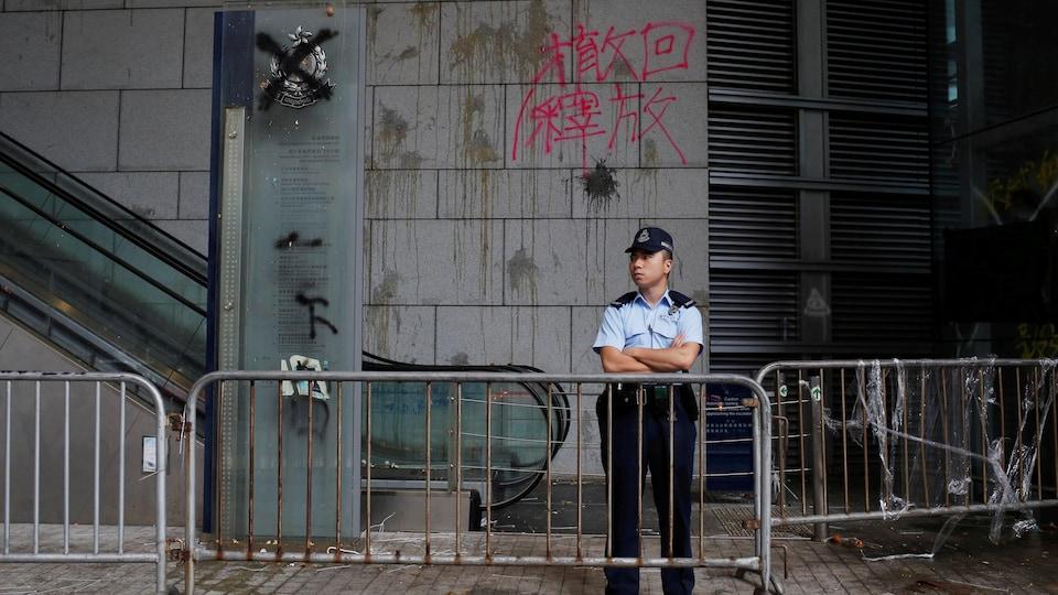 Des marques d'œufs et des graffitis anti-extradition sont visibles sur les murs du quartier général de la police hongkongaise. Une barrière de sécurité a été installée, et un policier veille à la sécurité du site.