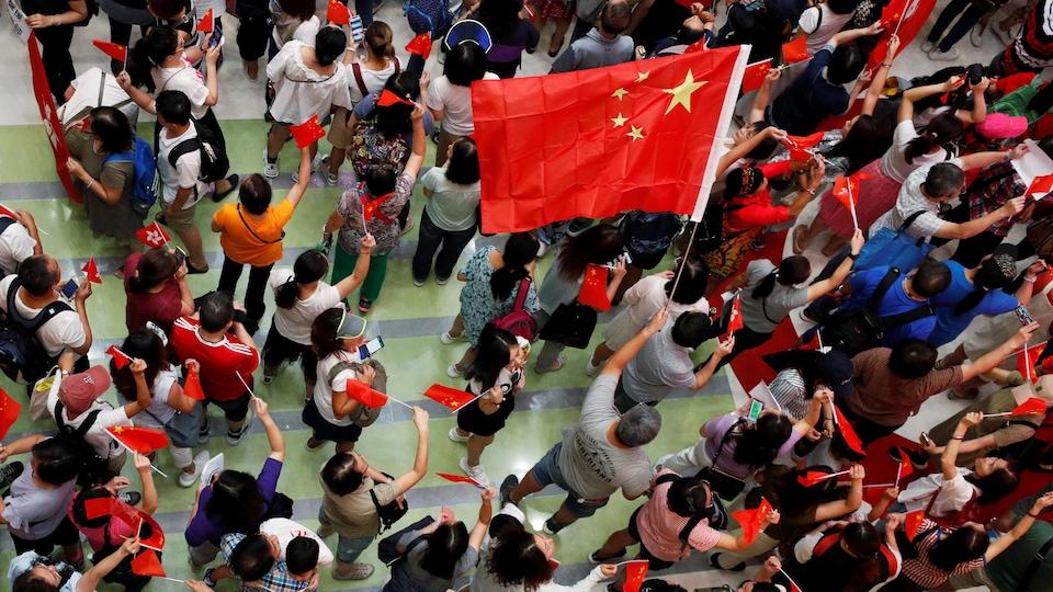Une foule vue de haut agite des drapeaux chinois