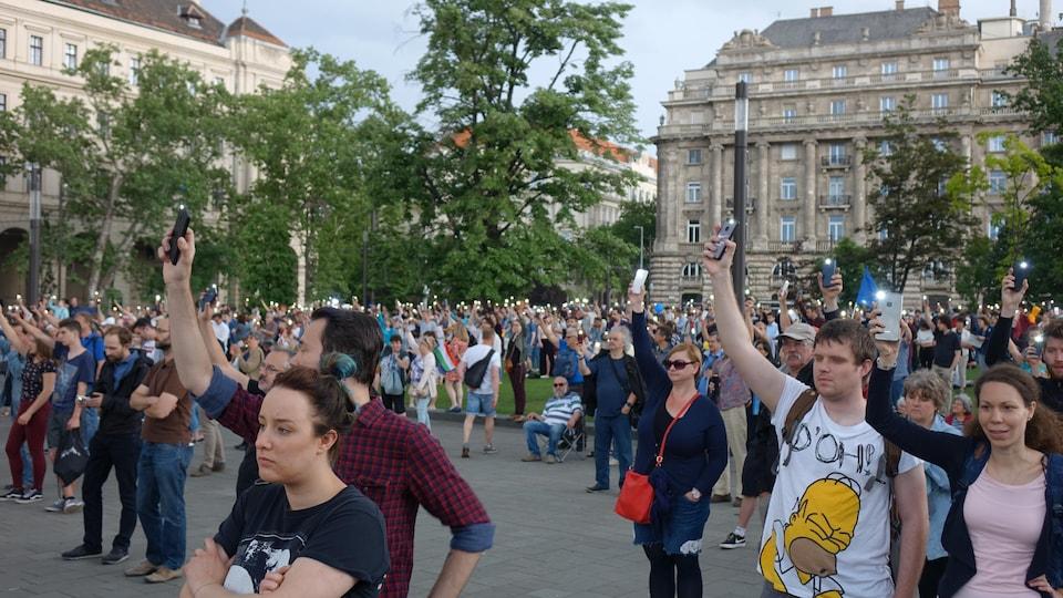 Des manifestants tiennent en l'air leurs téléphones en mode flashlight.