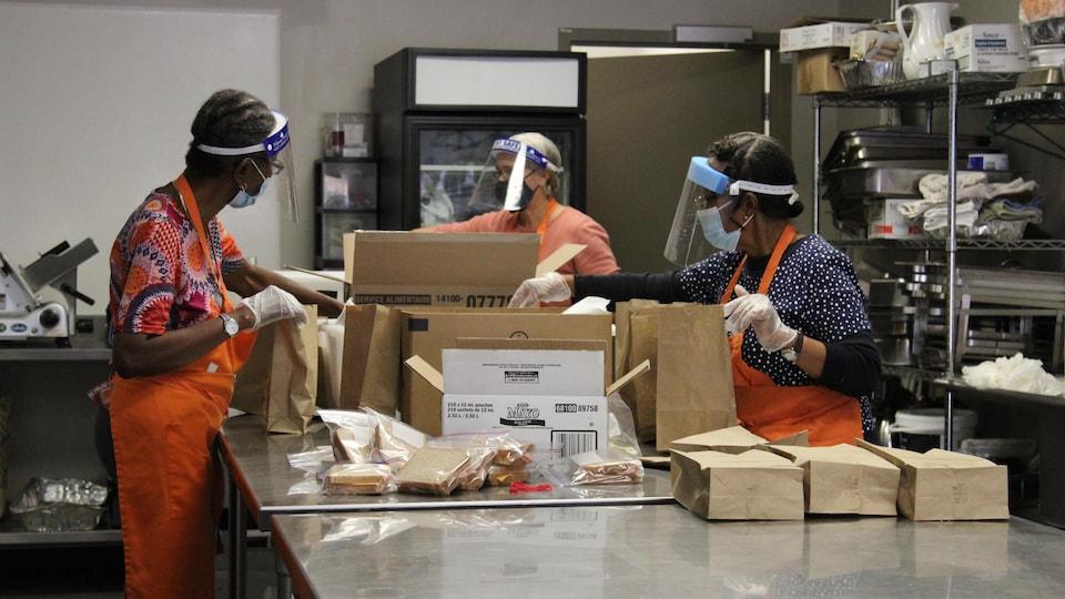 Des bénévoles préparent des repas dans une cuisine communautaire.