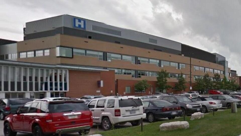 Vue extérieure d'un hôpital. Des voitures sont stationnées devant.