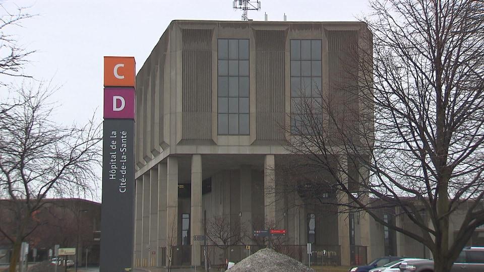Un panneau portant le nom de l'hôpital à la verticale devant un bâtiment en béton par une journée pluvieuse de printemps.