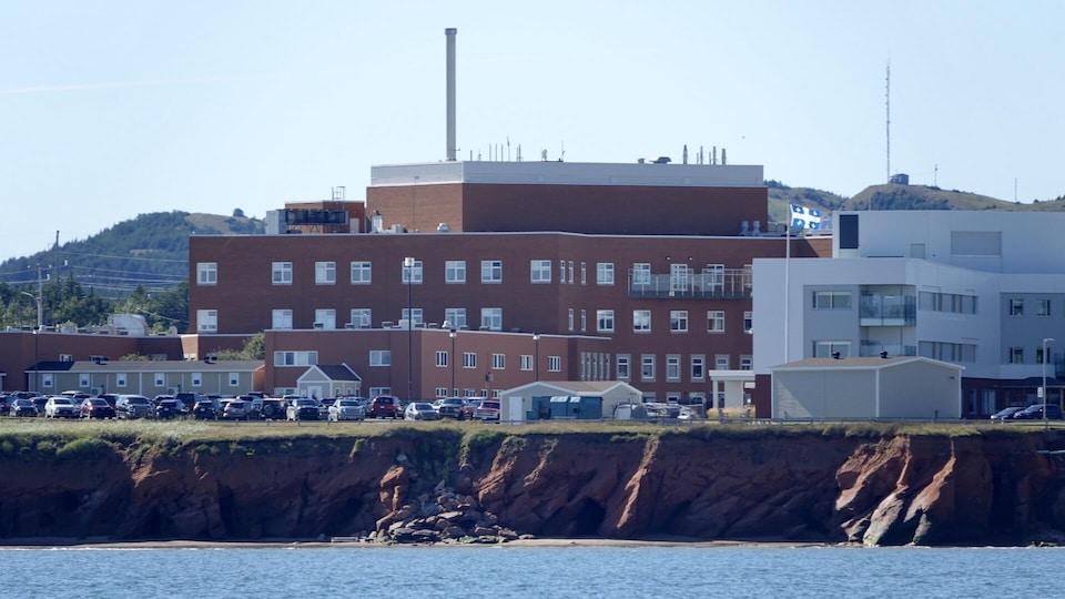 L'hôpital de Cap-aux-Meules, vu de la mer, avec une falaises érodée en avant-plan.