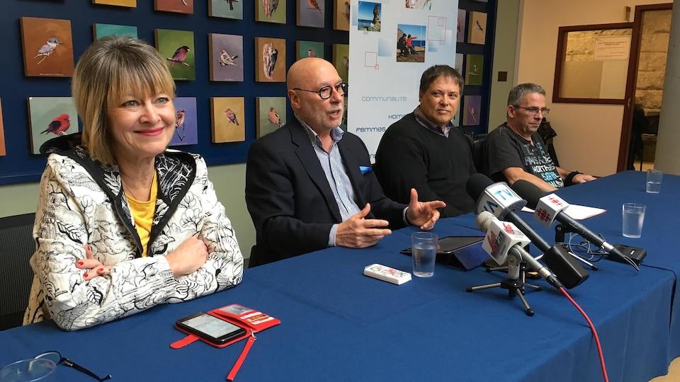 Quatre personnes assises à une table pour une conférence de presse.