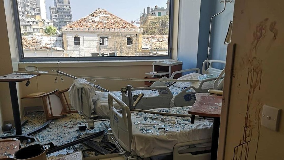 Debris and broken glass on the floor and on beds in a hospital room.