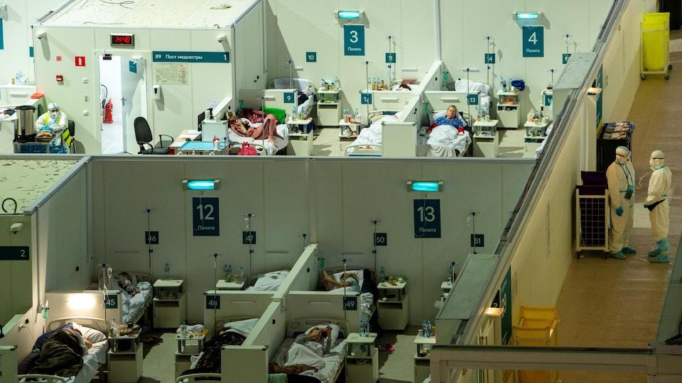 Une vue de haut de l'installation temporaire, où des patients dans des lits sont traités par des médecins en habits de protection.