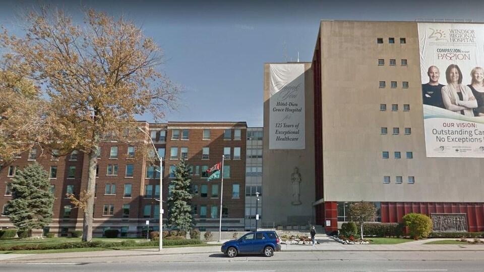 Vue extérieure d'un bâtiment. Une grande banderole publicitaire couvre un l'immeuble à droite.