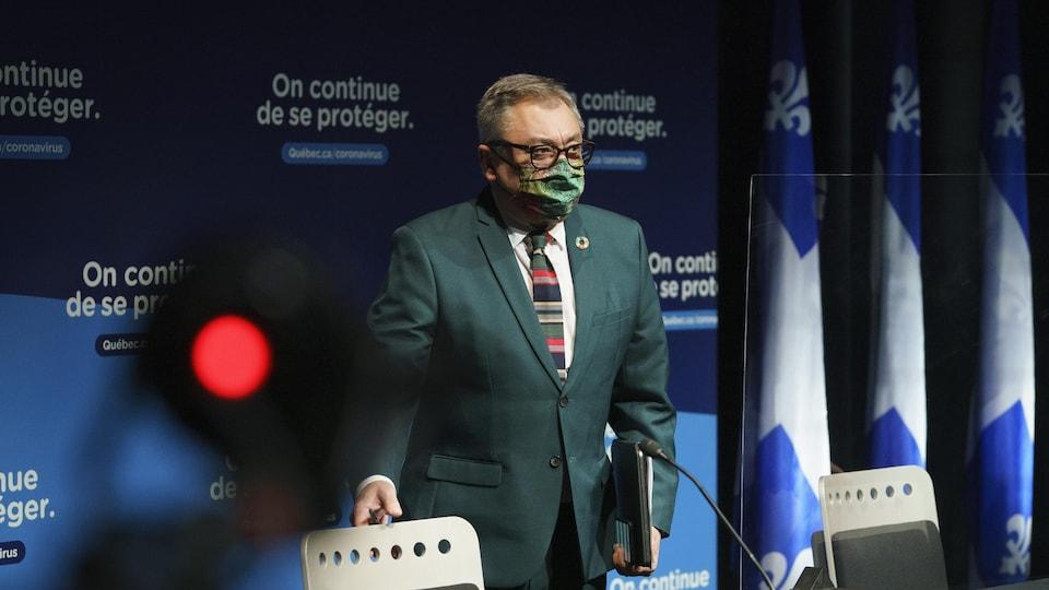Il porte un masque à son arrivée à une conférence de presse.