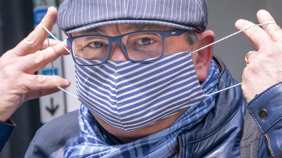 Le Dr Horacio Arruda mettant un masque en tissu.