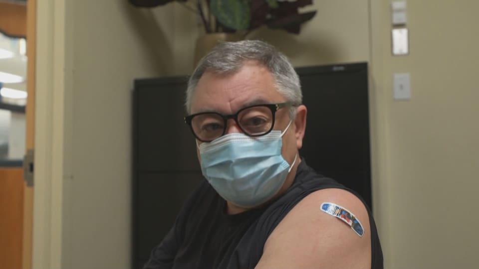 Le Dr Arruda porte des lunettes et un masque. Il a un diachylon sur l'épaule gauche.