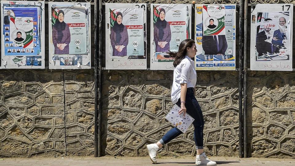 Une femme marche devant des affiches électorales