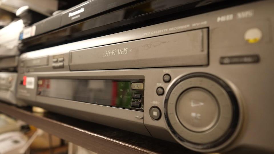 Un lecteur vidéocassettes sur une étagère.