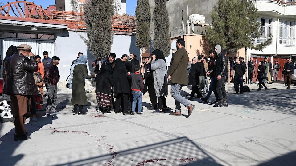 Plus d'une trentaine de personnes rassemblées sur les lieux, où des traînées de sang sont encore apparentes sur le sol.