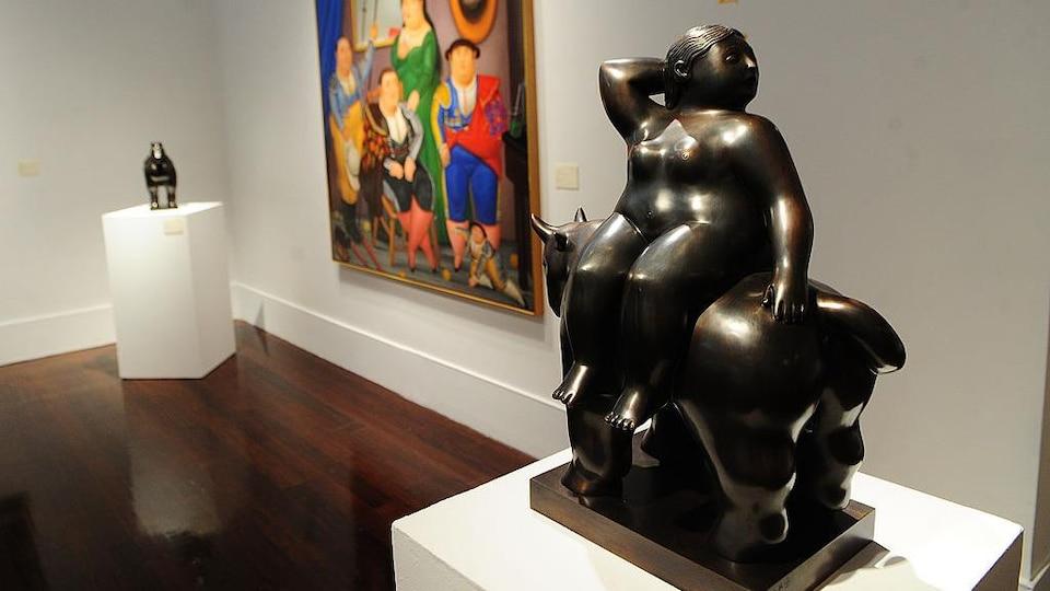 La sculpture de couleur foncée représente une femme assise sur un animale.