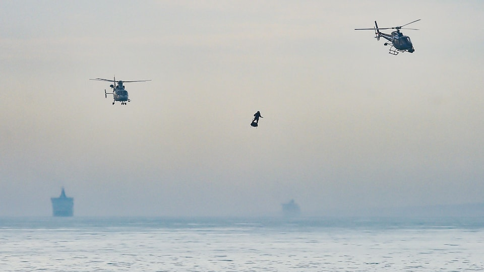 Franky Zapata sur son Flyboard au-dessus de la Manche, accompagné de deux hélicoptères.