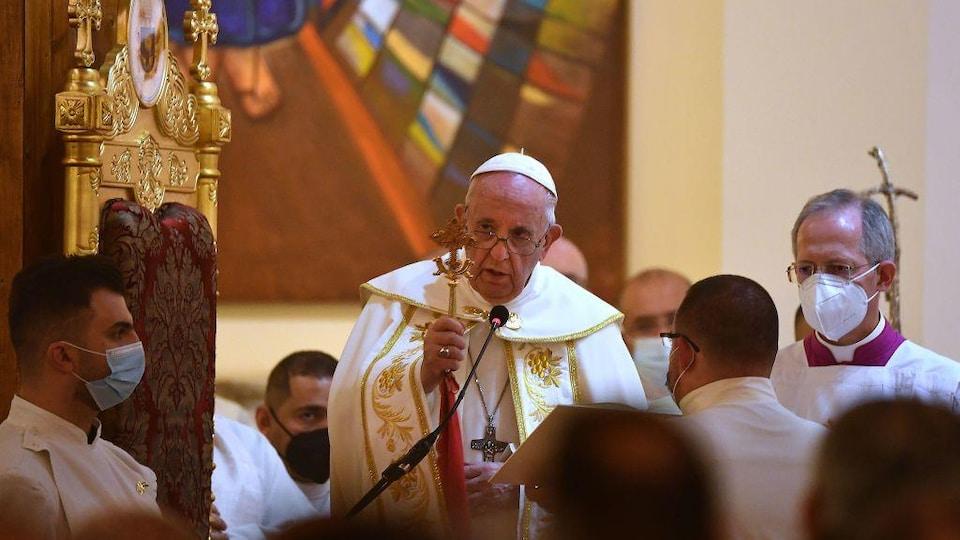 Le pape célèbre la messe, entouré d'hommes.