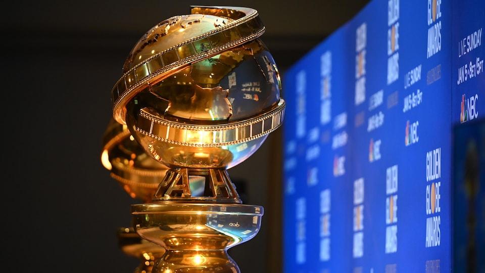 Deux trophées Golden Globes vus de près, devant un écran bleu.
