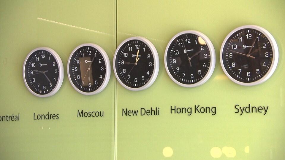Une série d'horloges montrent l'heure à Londres, Moscou, New Dehli, Hong Kong et Sydney.