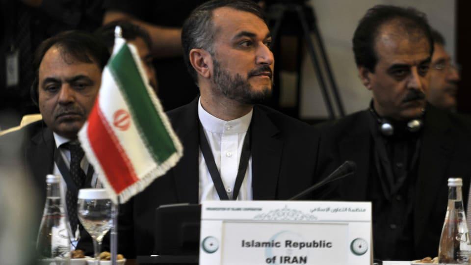 Hossein Amir-Abdollahian assis derrière un petit drapeau de l'Iran, entouré d'autres hommes.