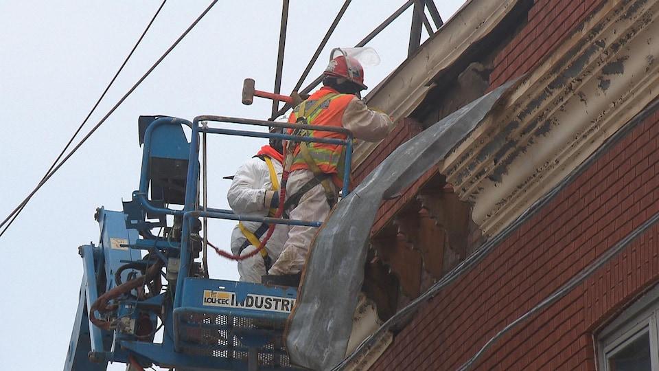 Des ouvriers enlevaient les briques une à une ou avec une masse.