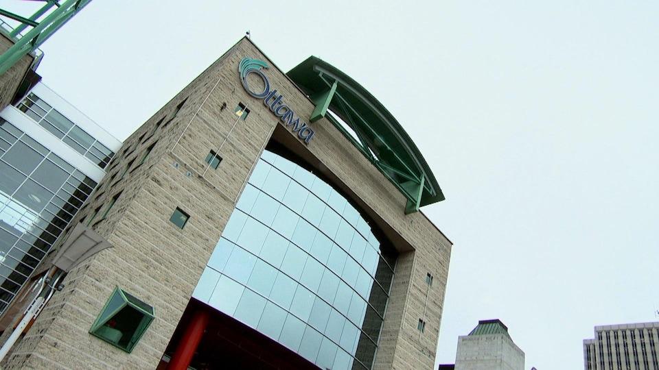 La façade en verre, avec le logo de la Ville, est prise en contre-plongée.