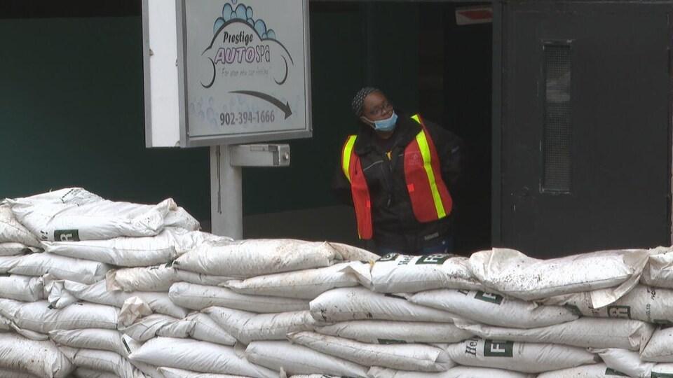 Des sacs de sable empilés devant une entrée et une préposée qui surveille les sacs.