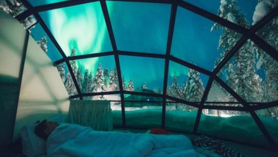 Un homme couché dans un lit sous un dôme de verre. Dans le ciel on voit des aurores boréales vertes et des arbres enneigés.
