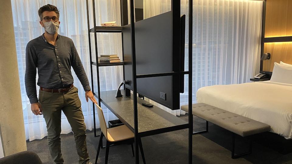 Un homme pose dans une chambre d'hôtel qui peut maintenant servir pour le télétravail.
