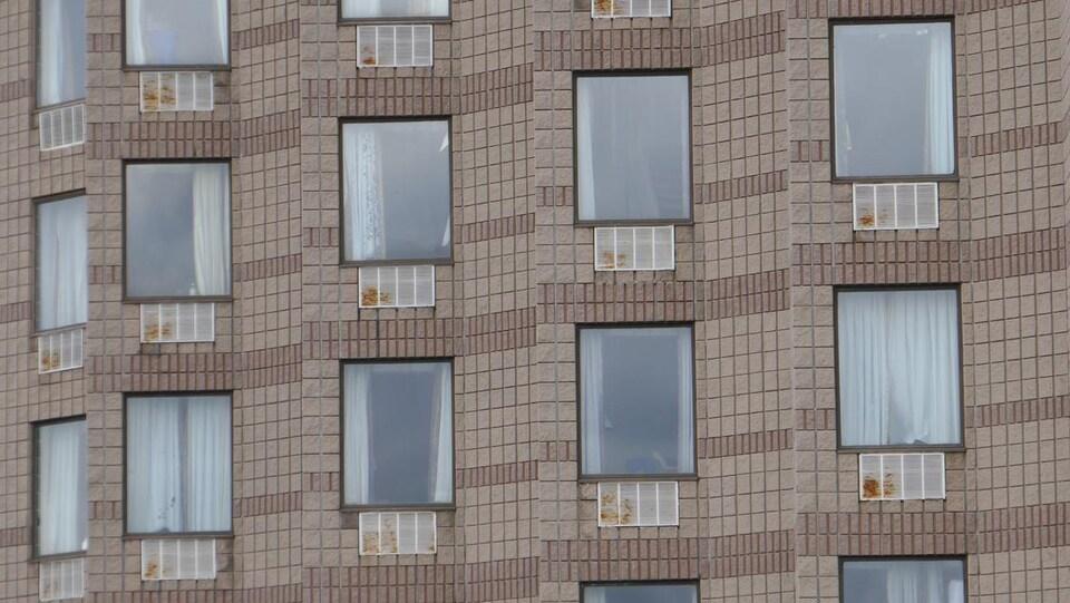 Un mur en briques brunes d'un hôtel; de la rouille est visible sur la couverture de métal de bouches d'aération.