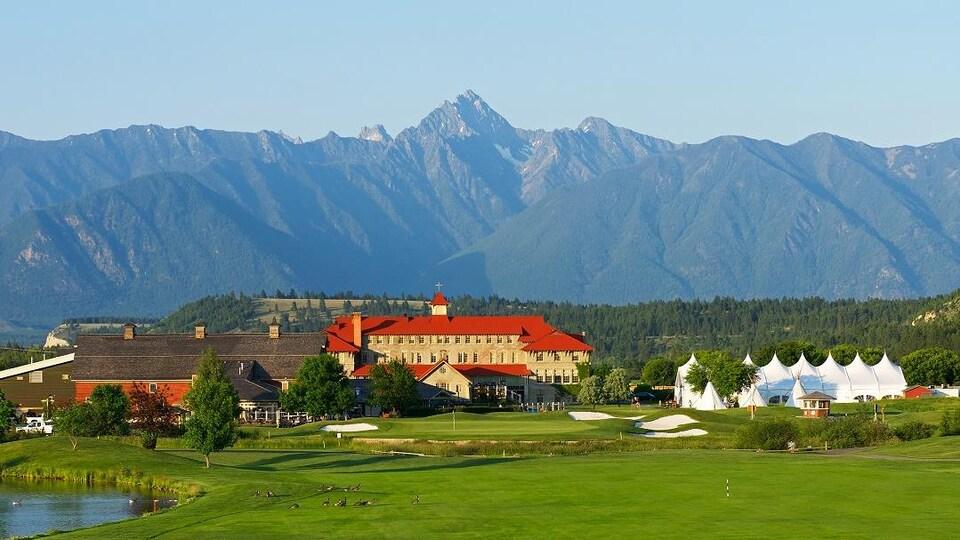 Un grand bâtiment entouré d'un terrain de golf et de montagnes.