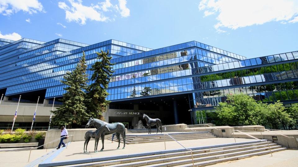 Sculptures de chevaux en métal avec un bâtiment vitré.
