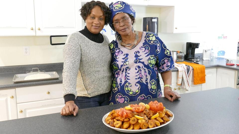 Oumou et Louise-Marie Akiki dans la cuisine devant le plat de bananes plantain frites au poulet.