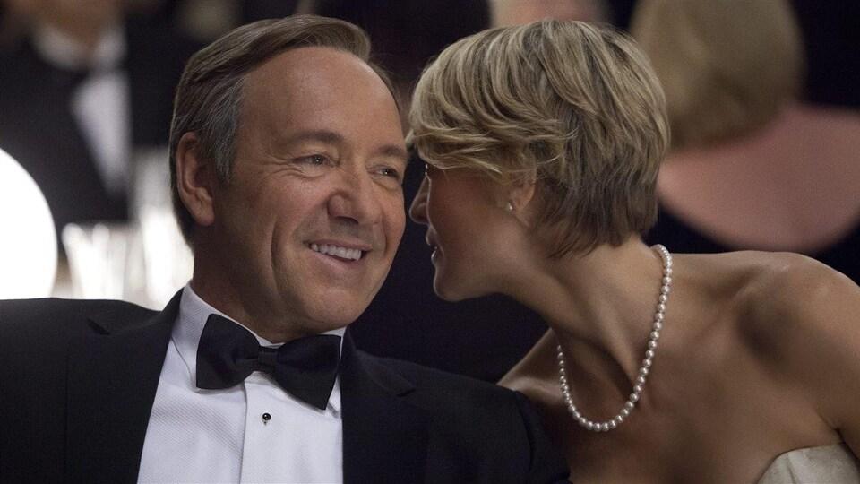 Le personnage Frank Underwood, sourire aux lèvres, pendant que sa femme, Claire, lui chuchote à l'oreille.
