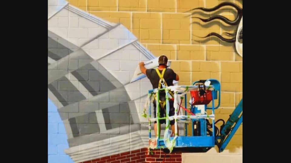 Allie Howe peint un paysage sur un mur extérieur.
