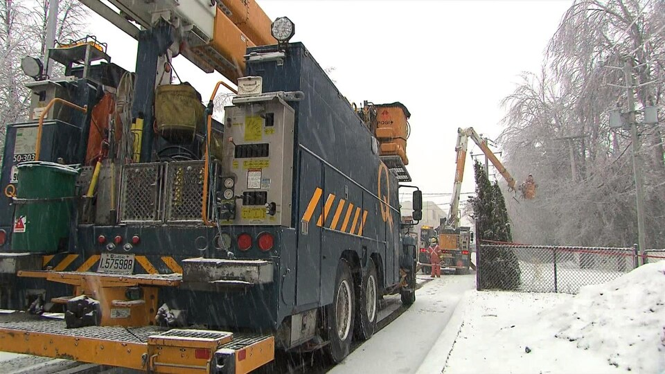 Deux camions d'Hydro-Québec et une nacelle déployée près des fils électriques.