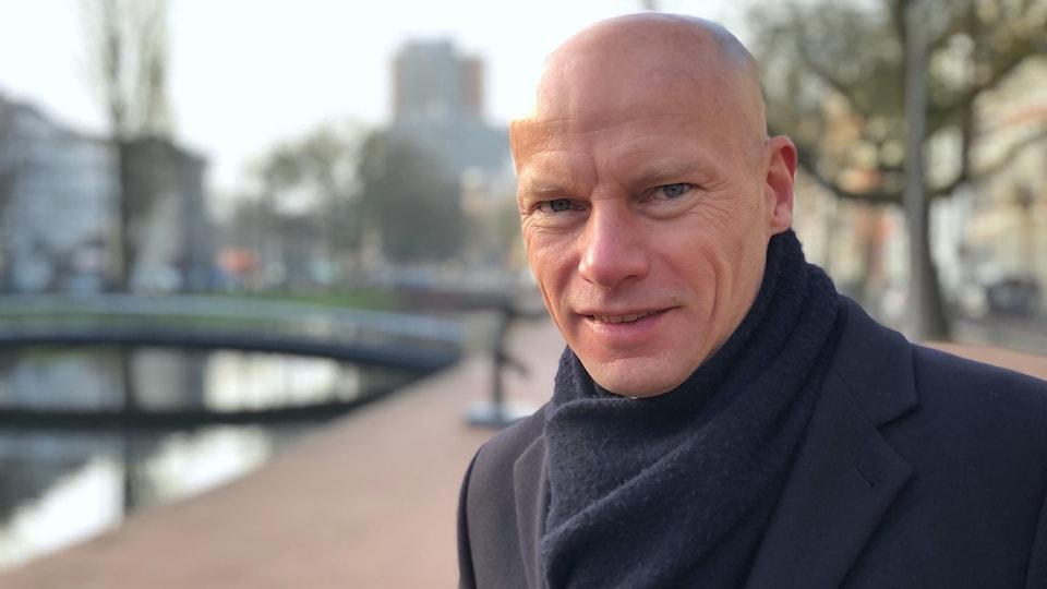 Henk Ovink se tient debout près d'un canal à Rotterdam.
